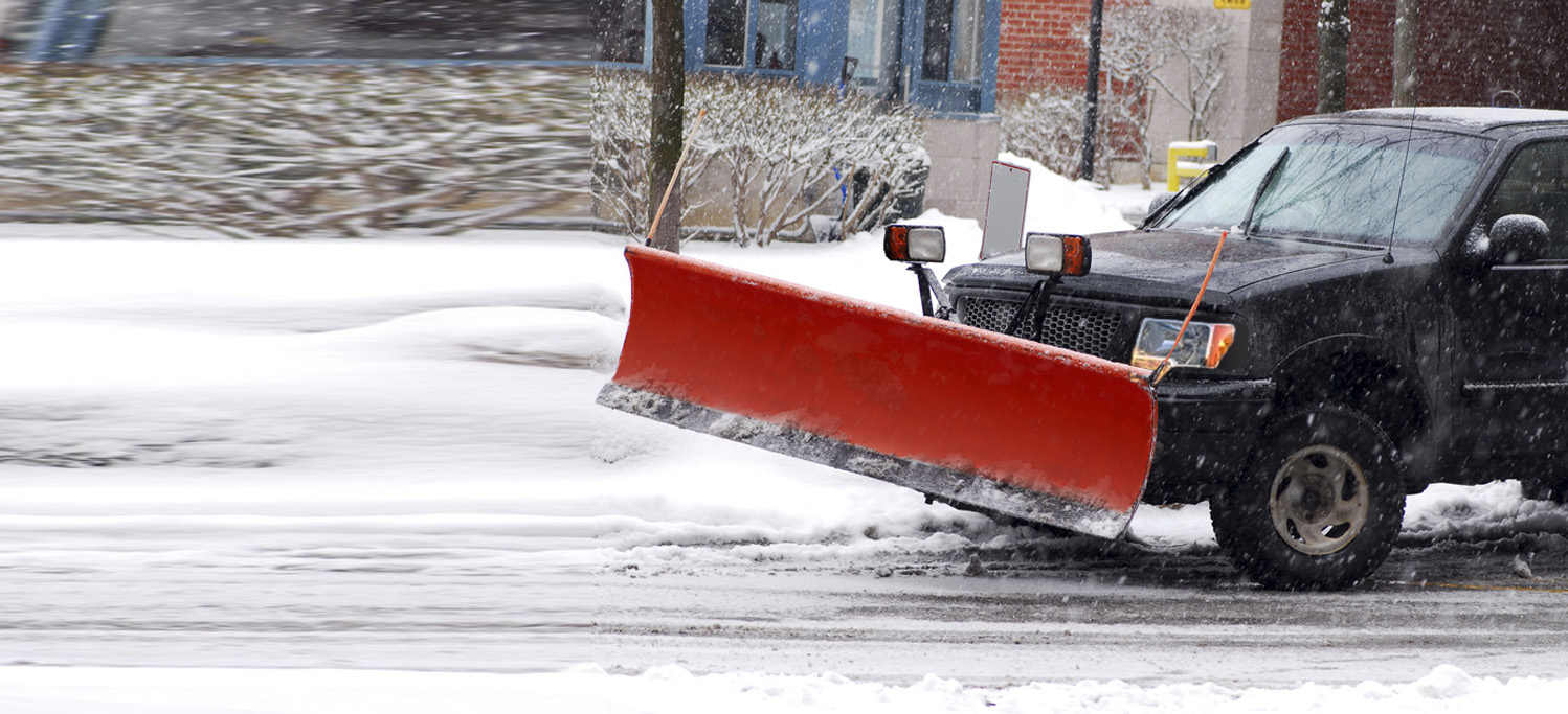 truck with red snow plow, plowing snow away from road