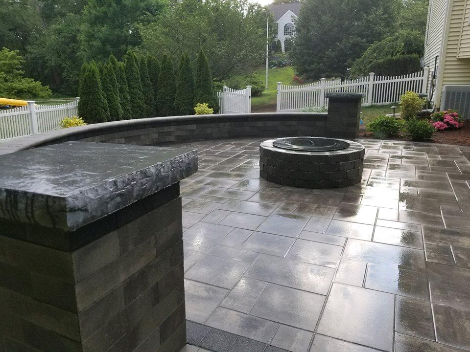 grey brick circular patio with brick fire pit